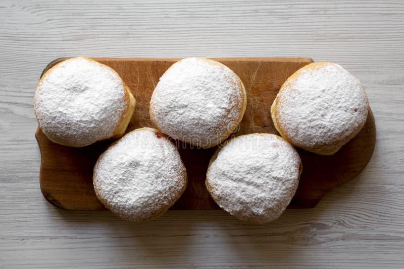 Domowej roboty smakowici donuts z galaretowym i sproszkowanym cukierem na nieociosanej drewnianej desce nad białym drewnianym tłe obrazy royalty free