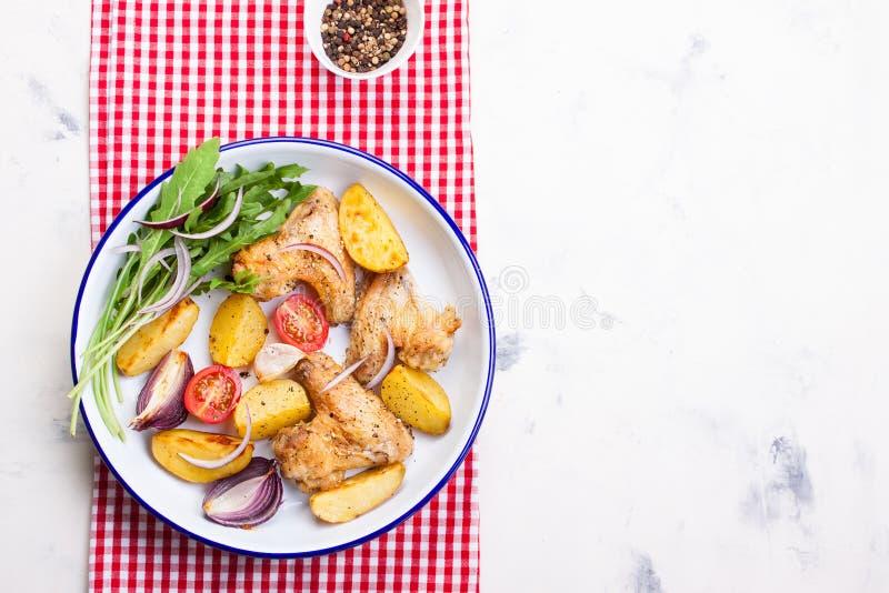 Domowej roboty smakowici piec kurczaków skrzydła z piec grulą z warzywami w emaliowym pucharze zdjęcia royalty free
