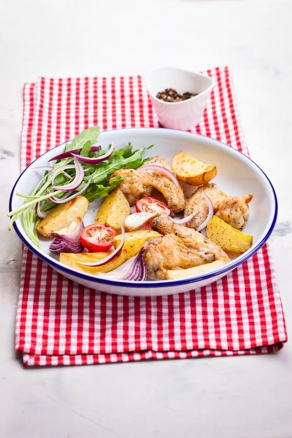 Domowej roboty smakowici piec kurczaków skrzydła z piec grulą z warzywami w emaliowym pucharze obrazy royalty free