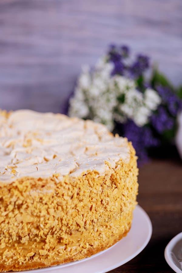 Domowej roboty tort z zdruzgotanymi dokrętkami i kwiatami na tle obrazy stock