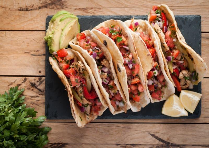 Domowej roboty tortillas z korzennym kurczakiem, warzywami i salsa, zamaczają na drewnianym stole, odgórny widok obrazy stock