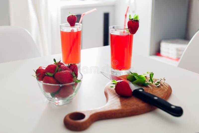 Domowej roboty truskawkowi koktajle z mennicą na kuchennym stole Lato napoje Zdrowy Styl życia zdjęcia stock