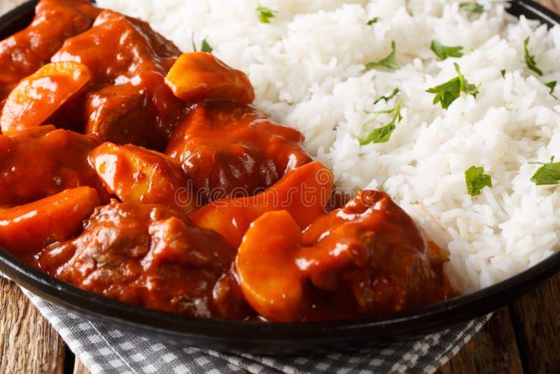 Domowej roboty wołowina gulasz z jabłkami w pomidorowym kumberlandzie słuzyć z ryżowym zbliżeniem na talerzu horyzontalny zdjęcie stock