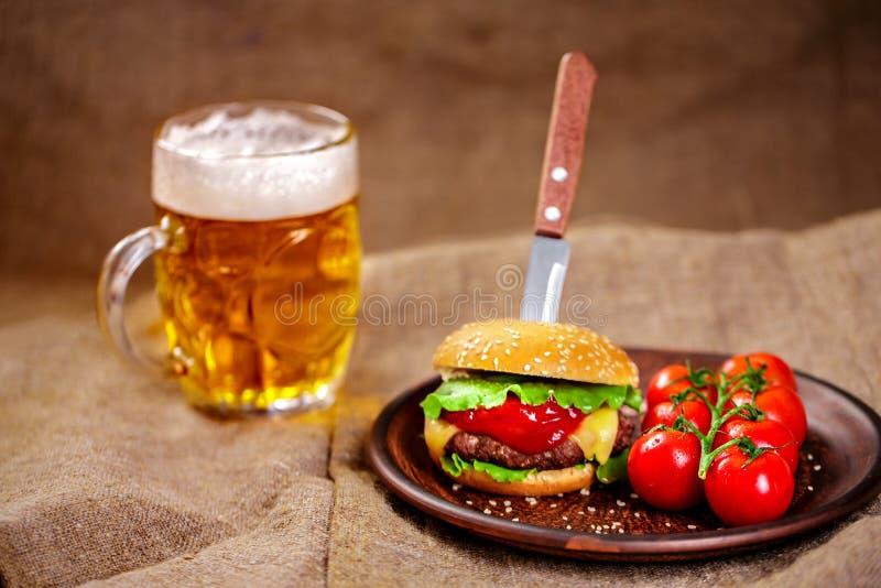 Domowej roboty wołowina hamburger i świezi warzywa na Glinianym naczyniu z szkłem piwo na nieociosanym drewnianym stole zdjęcie royalty free