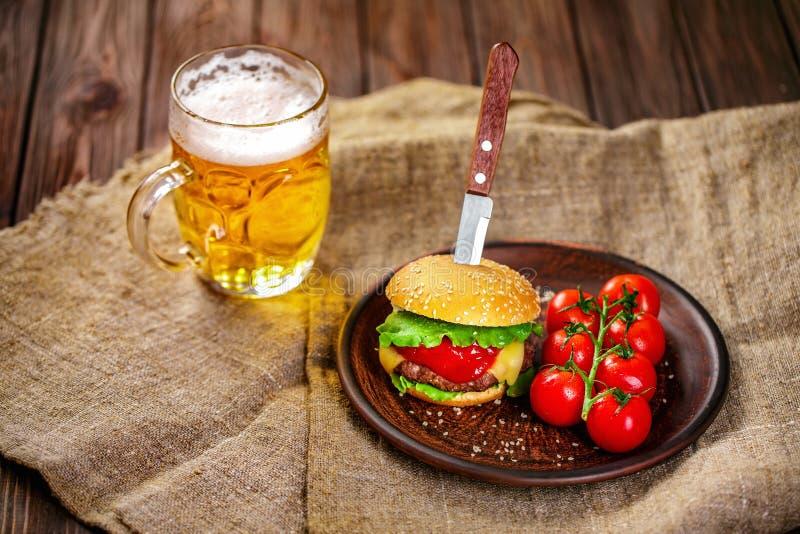 Domowej roboty wołowina hamburger i świezi warzywa na Glinianym naczyniu z szkłem piwo na nieociosanym drewnianym stole zdjęcia stock