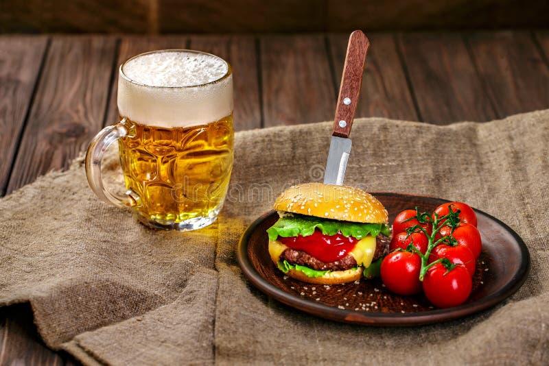 Domowej roboty wołowina hamburger i świezi warzywa na Glinianym naczyniu z szkłem piwo na nieociosanym drewnianym stole obraz stock