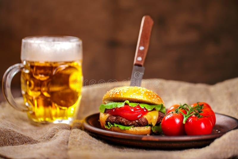 Domowej roboty wołowina hamburger i świezi warzywa na Glinianym naczyniu z szkłem piwo na nieociosanym drewnianym stole fotografia stock