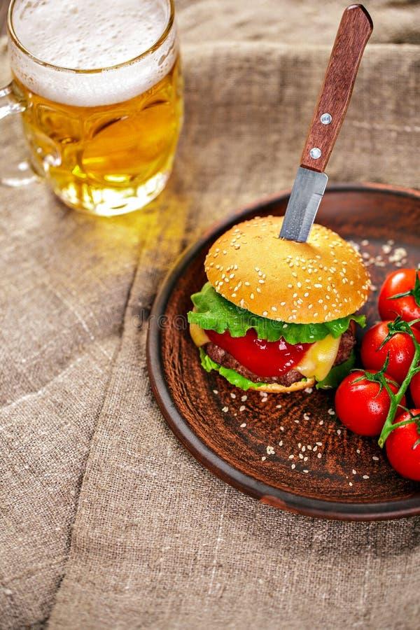 Domowej roboty wołowina hamburger i świezi warzywa na Glinianym naczyniu z szkłem piwo na nieociosanym drewnianym stole fotografia royalty free