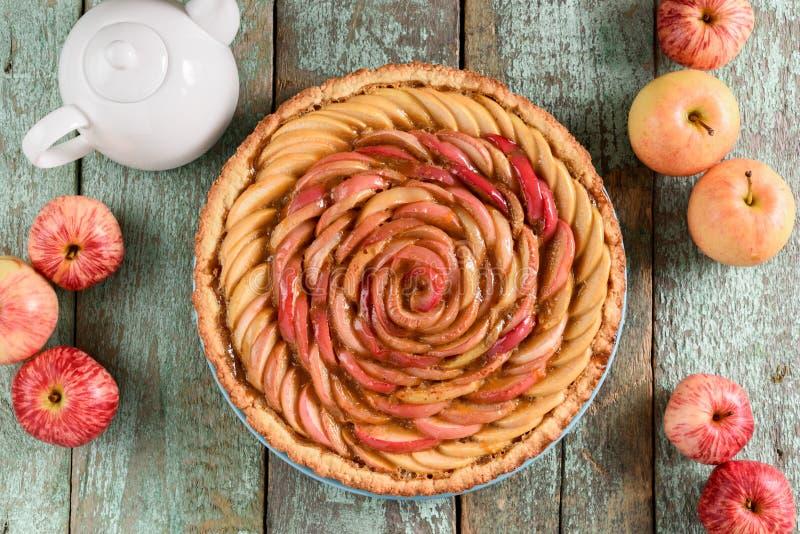 Domowej roboty wyśmienitego jabłka różany kulebiak z surowymi organicznie jabłkami na rusti zdjęcia stock