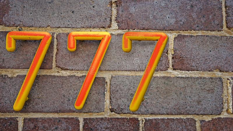 Domowi liczby siedemset i siedemdziesiąt siedem 777 na ściana z cegieł tle fotografia royalty free
