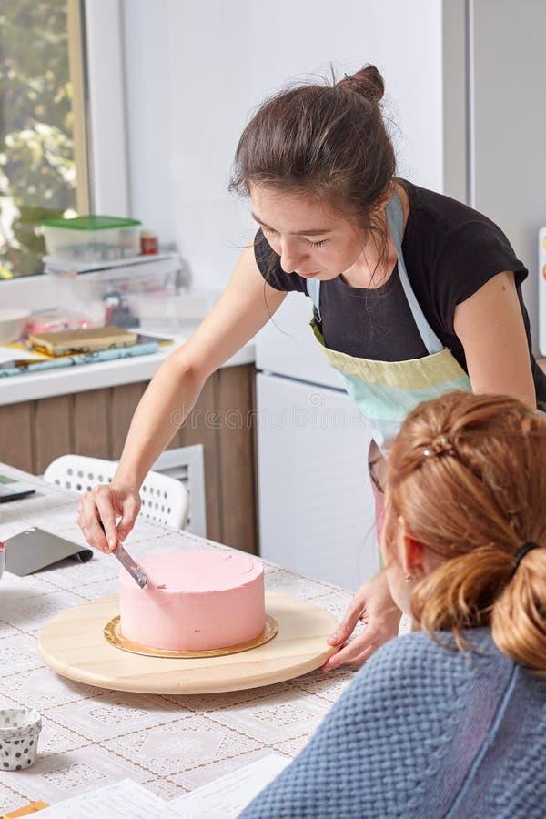 Domowy ciasto szef kuchni uczy dlaczego zrównywać tort z śmietanką zdjęcia stock