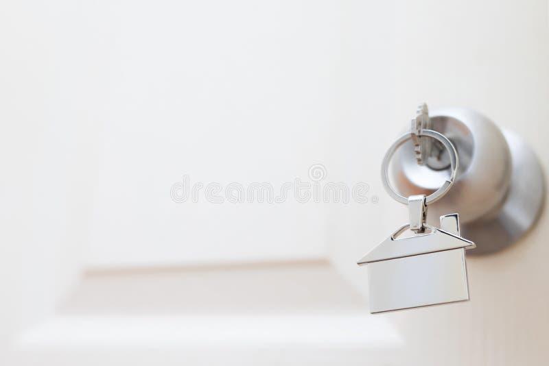 Domowy klucz na domowym kształtnym kluczowego łańcuchu srebra keyring w kędziorku drzwi obrazy royalty free