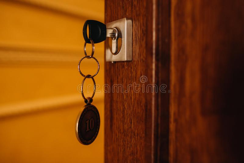 Domowy klucz w drzwi Klucz z kluczowym łańcuchem otwiera drewnianego drzwi lub zamyka zdjęcia royalty free