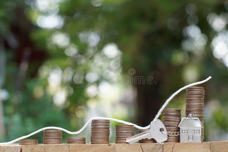 Domowy klucz z domowymi keyring monety stertami na drewnianym stole z plamy zieleni ogródu tłem, jaskrawym ranku koloru brzmienie obrazy stock