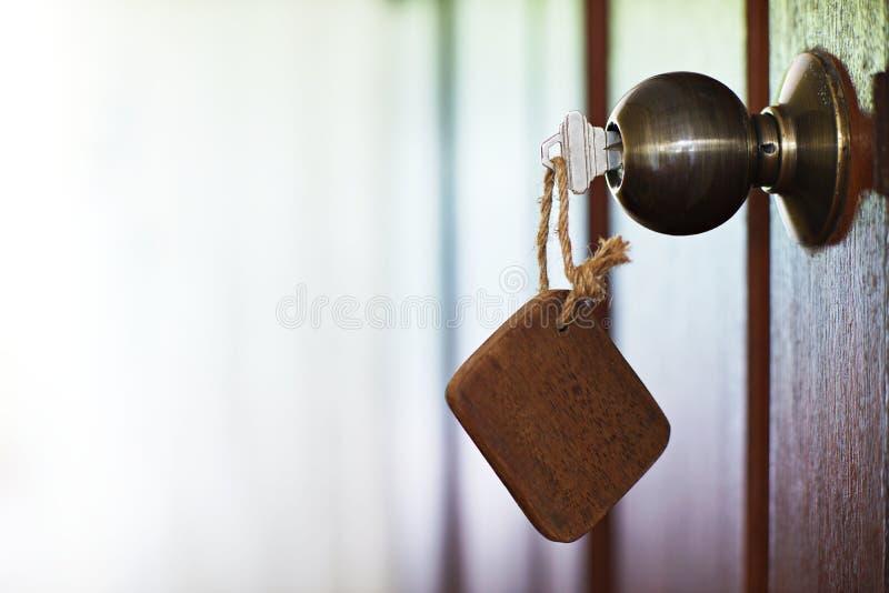 Domowy klucz z drewnianym puste miejsce domu keychain w keyhole, majątkowy pojęcie obraz royalty free