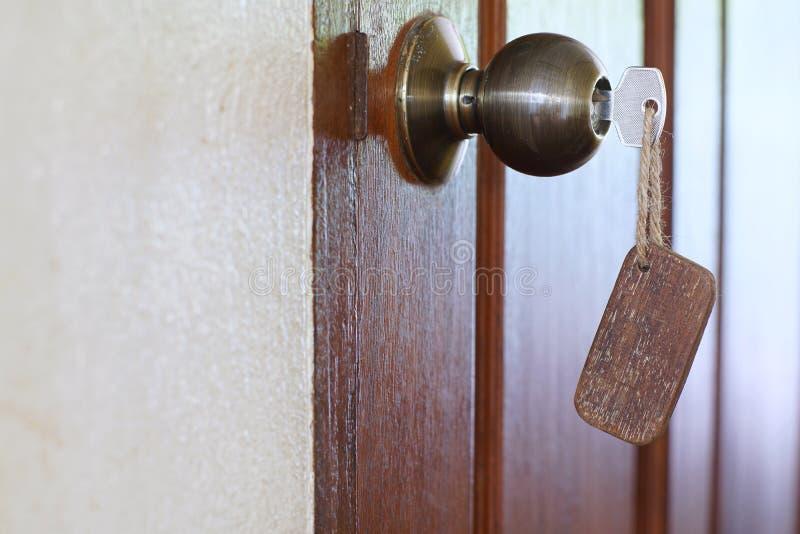 Domowy klucz z pustym drewnianym keychain w keyhole, majątkowy pojęcie zdjęcie royalty free
