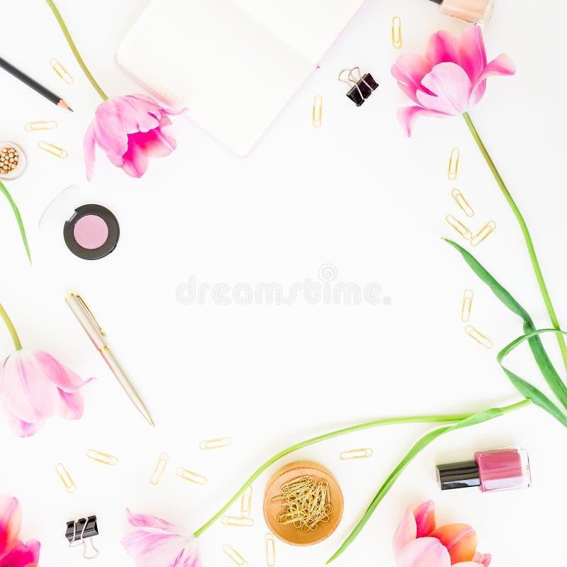 Domowy kobiecy workspace z schowkiem, notatnikiem, menchia kwiatami i akcesoriami na białym tle, Mieszkanie nieatutowy, odgórny w fotografia stock