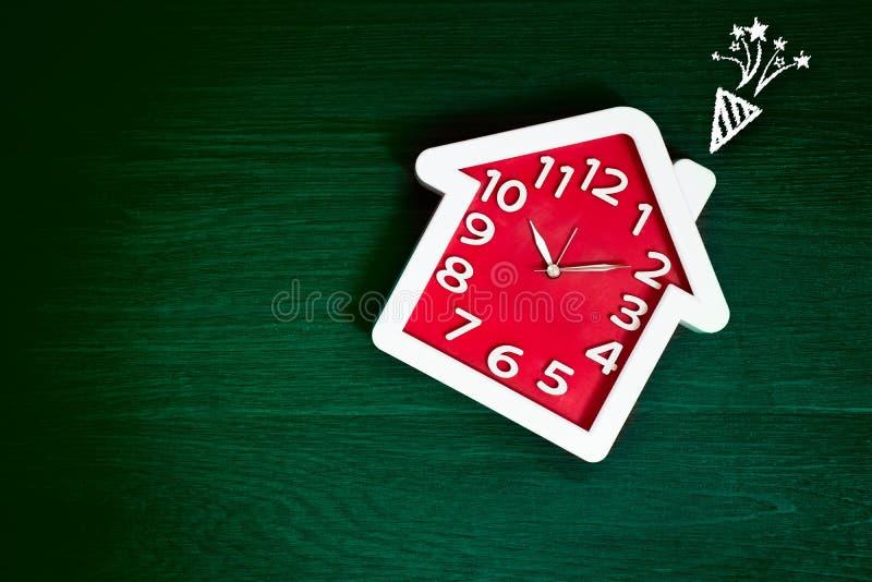 Domowy kszta?t czerwieni zegar na zielonym pod?ogowym tle z ?wi?towanie fajerwerku ikon? Szcz??liwy ?ycie i Rodzinny poj?cie Wnęt fotografia royalty free