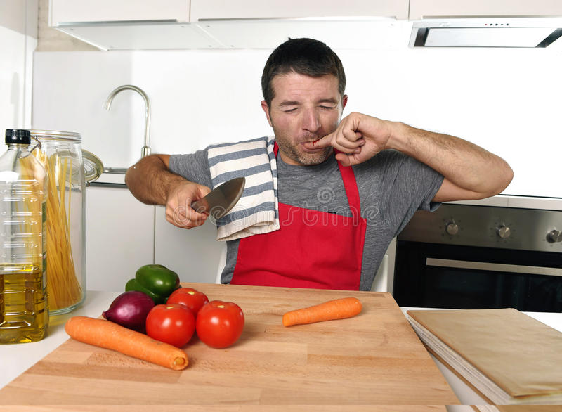 Domowy kucbarski mężczyzna cierpi domowego wypadkowego tnącego kaleczenie palec w czerwonej fartucha przecinania marchewce z kuch obraz royalty free