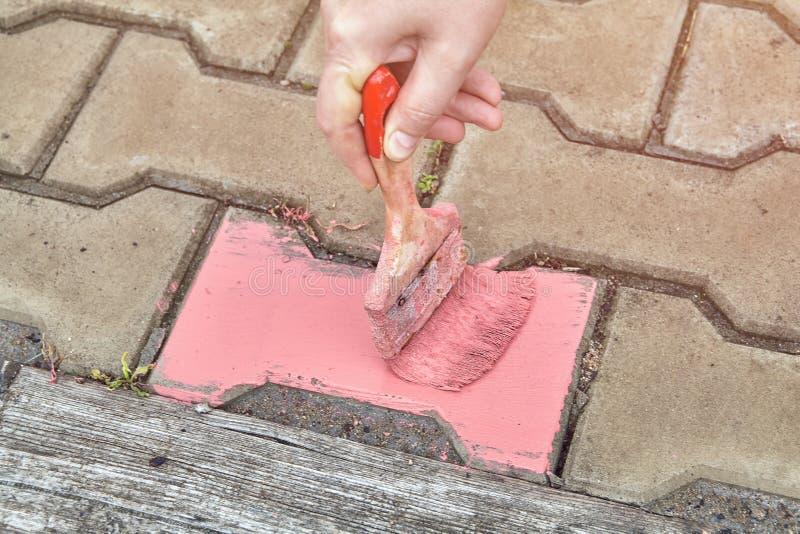 Domowy malarz używa paintbrush malować chodniczek w menchiach obraz royalty free