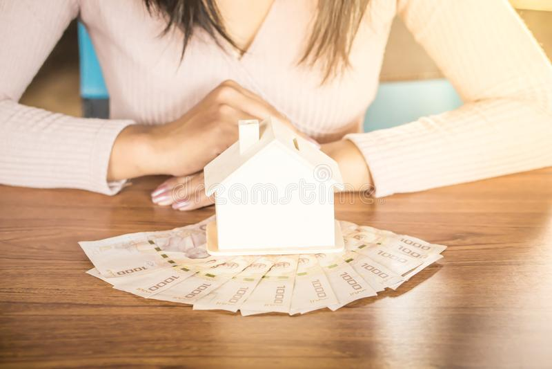 Domowy model i pieniądze na drewnianym stole z kobiety obsiadaniem w tła heblowaniu kupować do domu lub dzierżawić zdjęcia stock