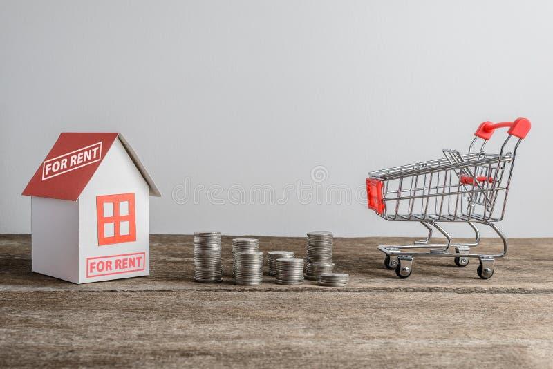 Domowy model i rząd menniczy pieniądze i wózek na zakupy obrazy stock
