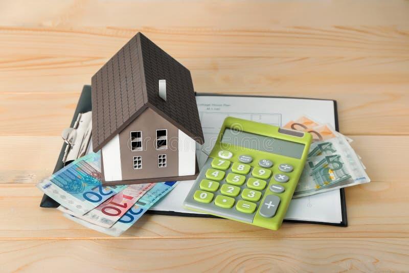 Domowy model, kalkulator i banknoty na drewnianym stole, 100 rachunk?w poj?cia dolara dom robi? hipotekuje robi? zdjęcia royalty free