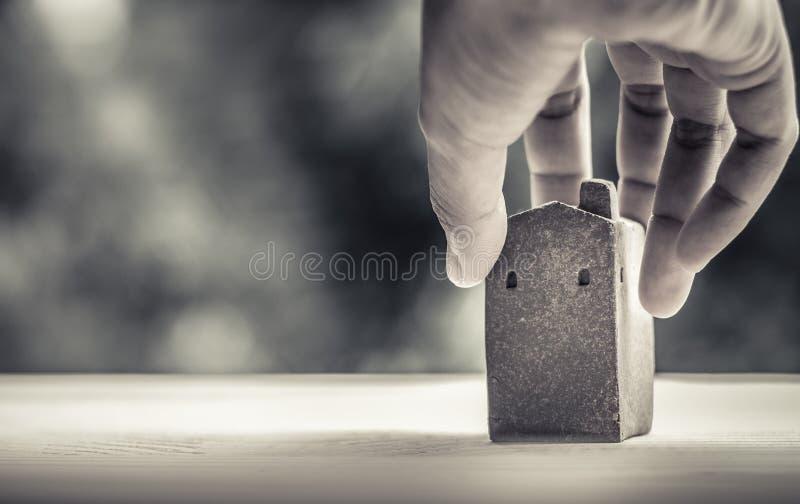 Domowy model robić od gliny na drewnianej powierzchni, trzyma prawą ręką, zamazywał bokeh jako tło, pożyczka z banku dla budowa d zdjęcia stock
