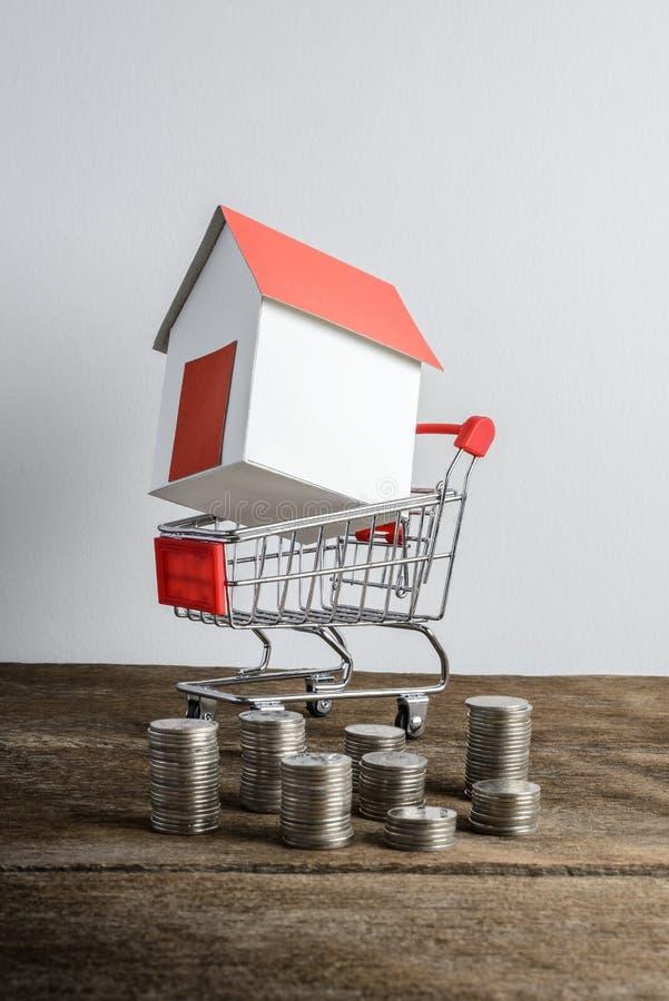 Domowy model w wózek na zakupy i rzędzie menniczy pieniądze fotografia stock