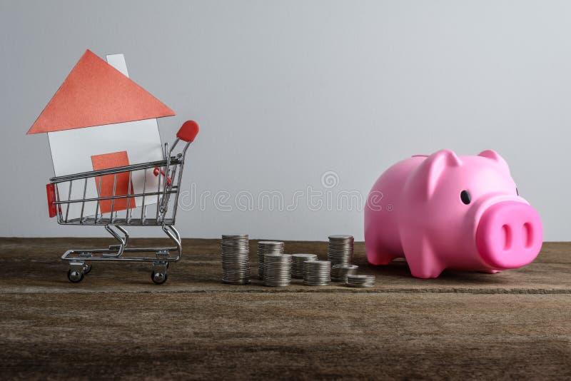 Domowy model w wózek na zakupy i rzędzie menniczy zakaz pieniądze i prosiątka obraz stock