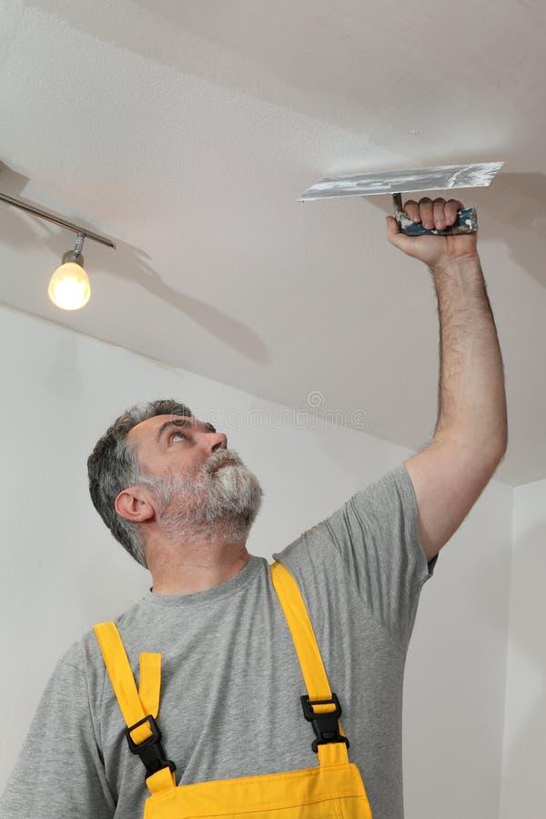 Domowy odświeżanie, pracownika naprawiania tynk przy sufitem obrazy stock