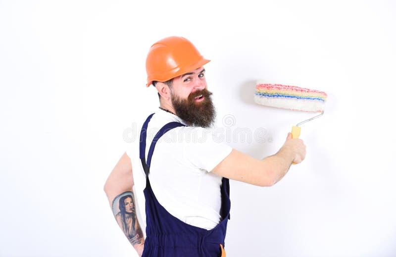 Domowy odmalowywania pojęcie Obraca z powrotem uśmiechać się budowniczego obrazu ścianę z farba rolownikiem Odosobniony mężczyzna fotografia stock