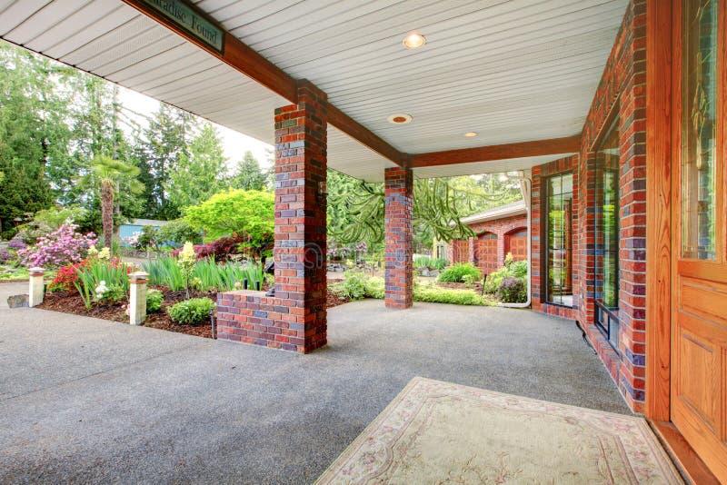 Domowy przód zakrywający ganeczek z drewnianym drzwi i wiosna krajobrazem. obrazy royalty free