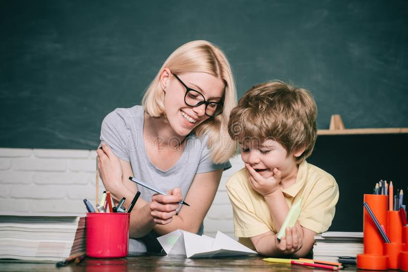 Domowy uczyć kogoś lub szkoła płatna Nauczycieli pomaga dzieciaki z ich prac? domow? w sala lekcyjnej przy szko?? Dziecko W Wieku zdjęcie royalty free