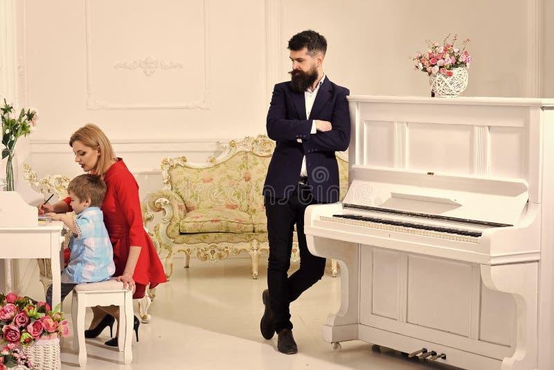 Domowy uczy kogoś pojęcie Rodzice cieszy się rodzicielstwo, szczęśliwego Ojciec stoi blisko pianina, ogląda podczas gdy matka ucz zdjęcie stock