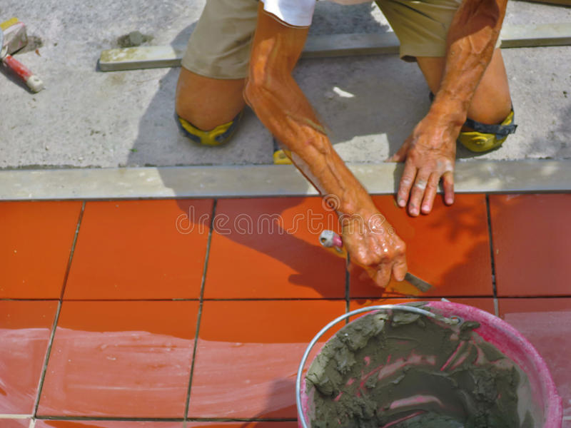 Domowy ulepszenie, odświeżanie - pracownika budowlanego kaflarz tafluje, ceramiczna dachówkowa podłoga adhezyjna fotografia stock