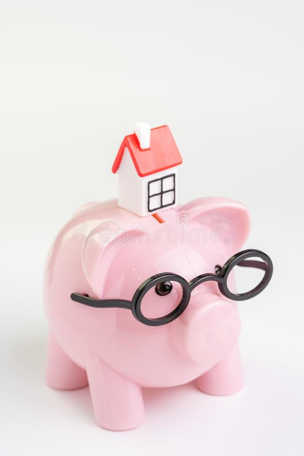 Domowy utrzymanie budżet, koszt, oszczędzania lub hipoteczny kredyta mieszkaniowego pojęcie, miniatura dom na różowym prosiątko b obraz royalty free