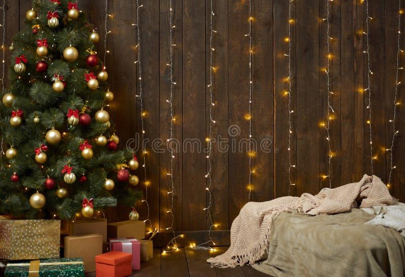 Domowy wnętrze z drewnianą ścianą, łóżkiem, choinką i światłami, obraz royalty free