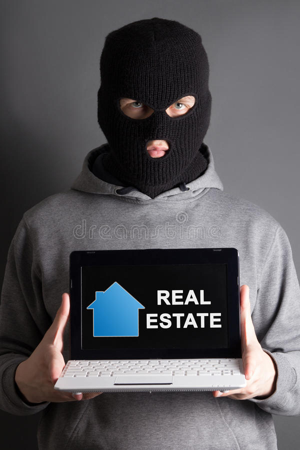 Domowy zbawczy pojęcie - zamaskowany mężczyzna mienia komputer z istnym estat zdjęcia royalty free