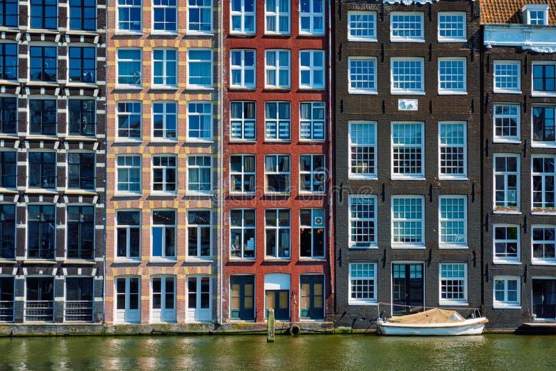 domy i łódź na Amsterdam kanałowy Damrak z odbiciem ams fotografia royalty free