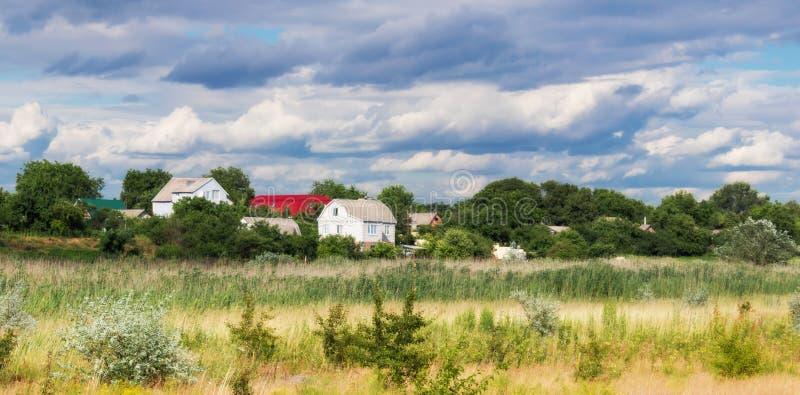 Domy wśród pięknego nieba i drzew zdjęcia royalty free
