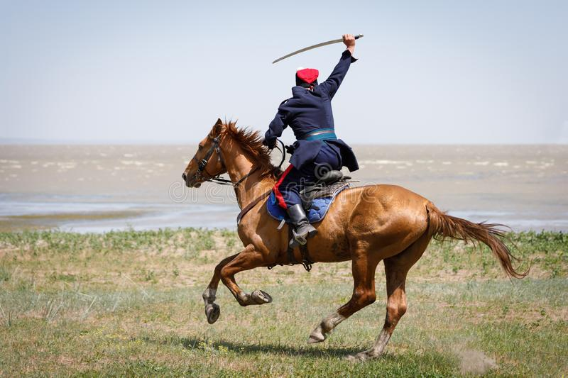 Don Cossack fast rides along the seashore on a horse with a sabre in his hand stock photography