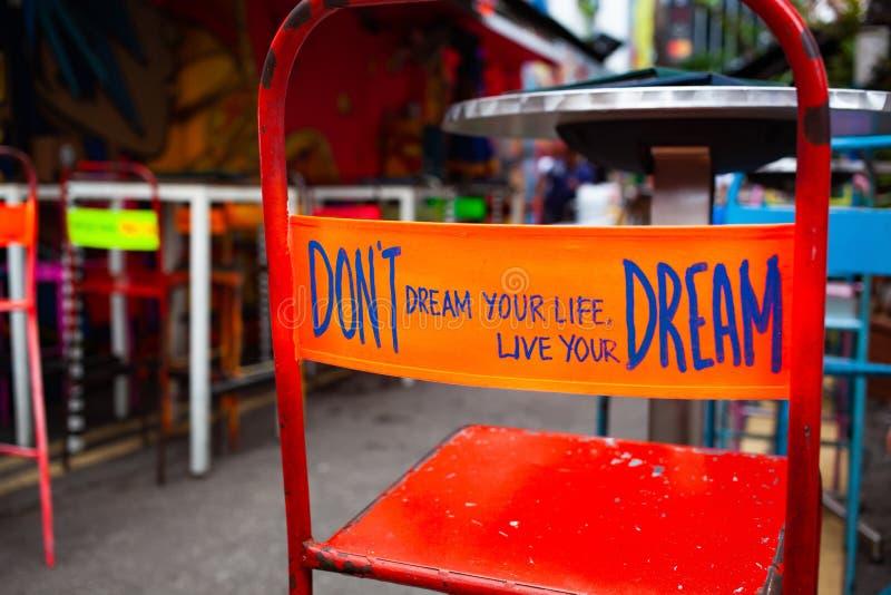 don& x27; el sueño de t su vida, vive su sueño - mensaje en la parte de atrás de una silla roja imagen de archivo libre de regalías