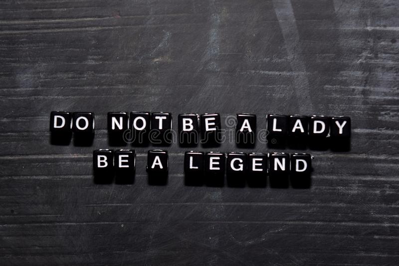 Don`t be a lady. Be a legend on wooden blocks. Education, Motivation and inspiration concept stock photography