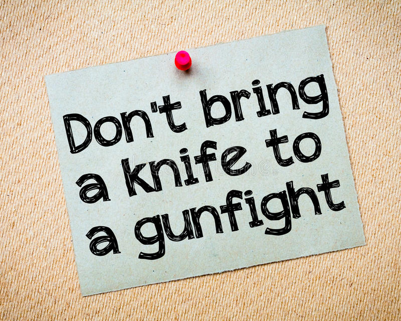 Don't bring a knife to a gunfight. Message. Recycled paper note pinned on cork board. Concept Image royalty free stock image
