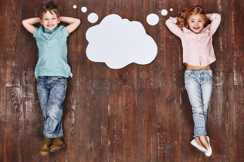 Don`t call it a dream, call it a plan. Children lying near empty thought cloud, looking at camera and smiling stock images
