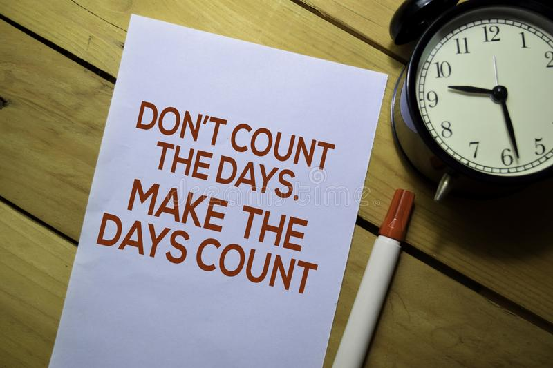 Don`t Count The Days. Make The Days Count text on the paper isolated on table background royalty free stock image