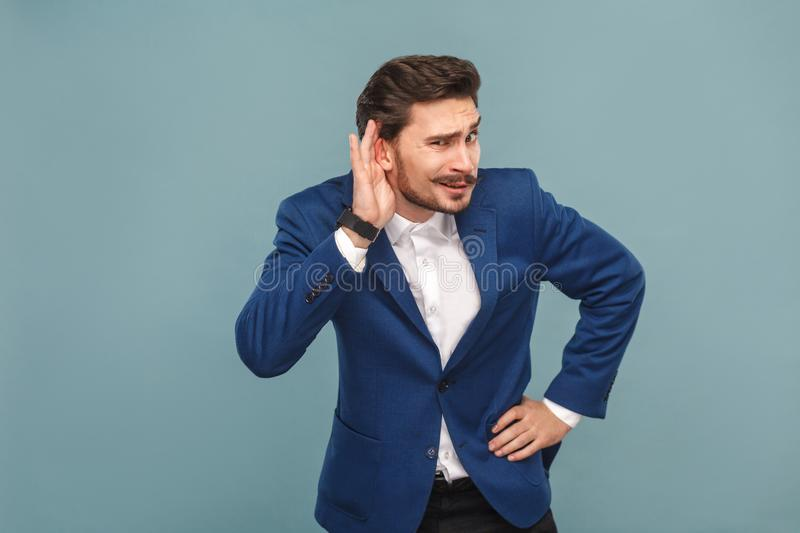 Don`t hear you. Secret news. Business people concept, richly and success. Indoor, studio shot on light blue background royalty free stock photos