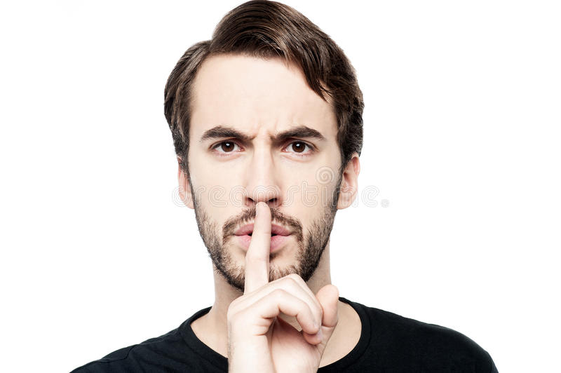 Don't make noise. Young man with finger on lips asking for silence royalty free stock photo