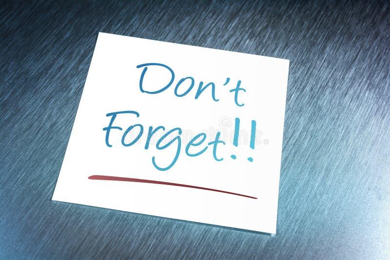 Don& x27; t olvida recordatorio en el papel que miente en el aluminio Brushed foto de archivo libre de regalías